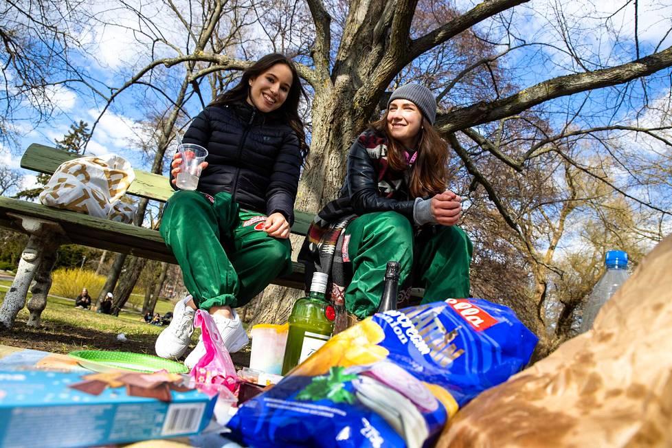 Sairaanhoitajaopiskelijat Hanne Nanouche ja Eeva Pohto istuskelivat sipsien ja siman voimalla Sibeliuksenpuistossa Töölössä.