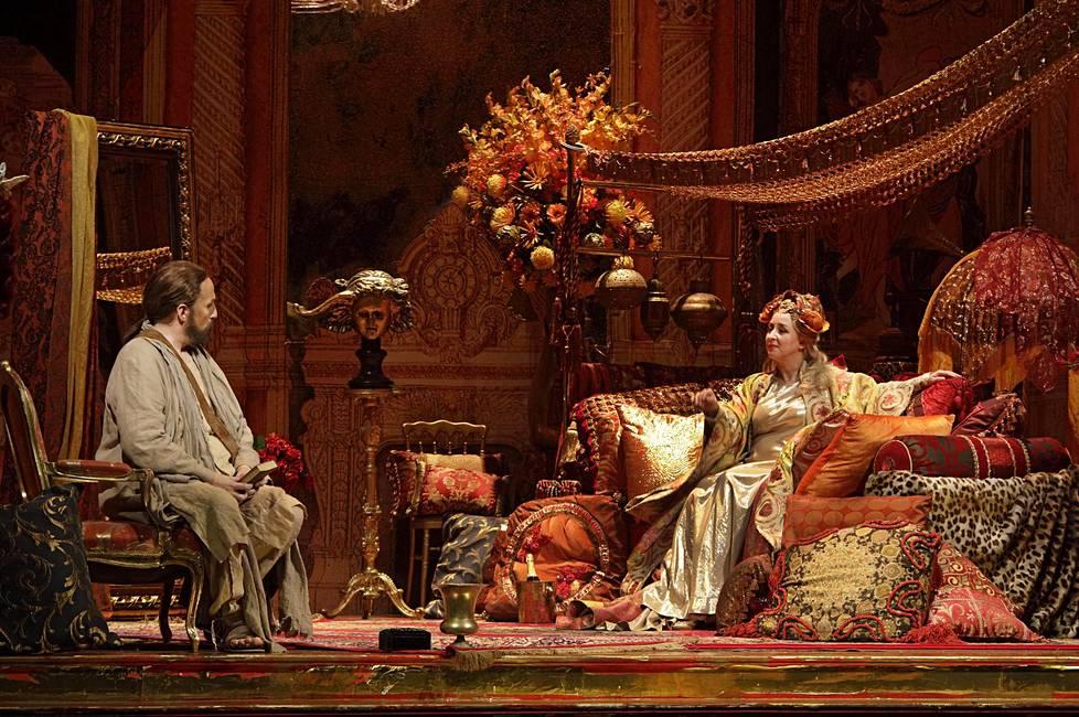 Munkki Athanaël (Warwick Fyfe) haluaa houkutella kurtisaani Thaïsin (Marianne Fiset) pois aistien valtakunnasta.