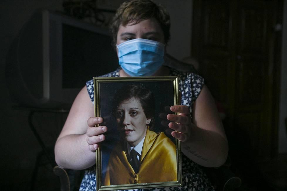 Espanjalainen Carla Muñoz Roblero, 28, esittelee koronaviruksen aiheuttamaan tautiin kuolleen tätinsä Isabel Muñoz Martínin valokuvaa. Hän työskenteli terveyskeskuslääkärinä.