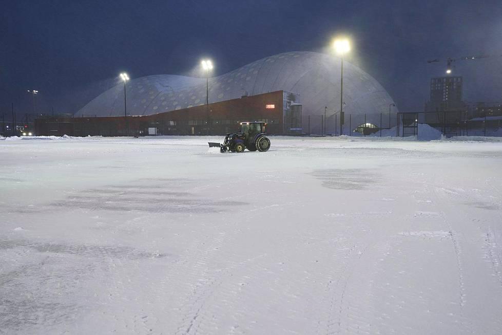 Jätkäsaaren liikuntapuiston tekonurmikenttää aurataan 12. tammikuuta 2021.