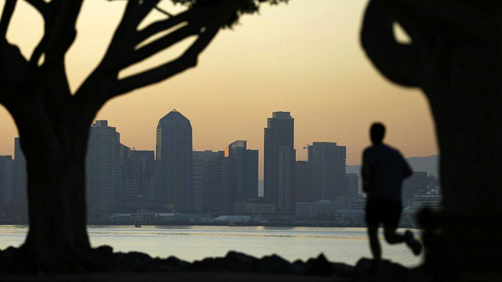 A jogger runs along a park in front of the skyline of San Diego, California September 12, 2014. REUTERS/Mike Blake (UNITED STATES - Tags: CITYSCAPE ENVIRONMENT SOCIETY) - RTR461IV