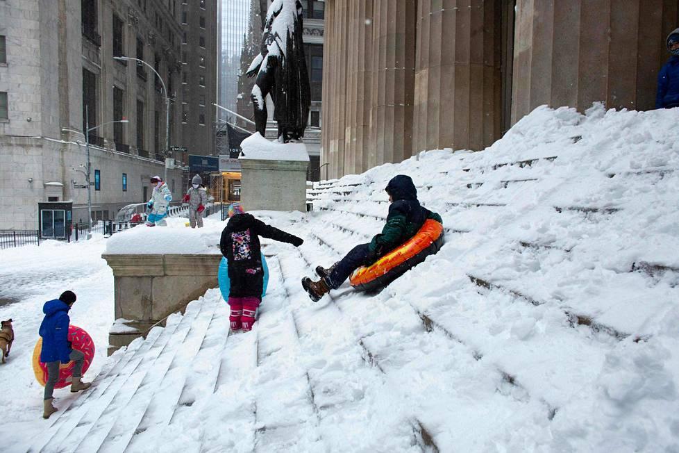 Lapset laskevat pulkkamäkeä Wall Streetillä.