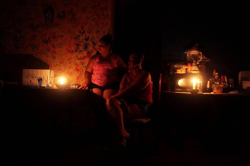 Jaimy Liz Villarini (vas.) ja Magda Rodriguez istuivat kynttilänvalossa kotonaan Puerto Ricon Vega Altassa. Maria-hurrikaani vei heiltä sähköt syyskuussa.