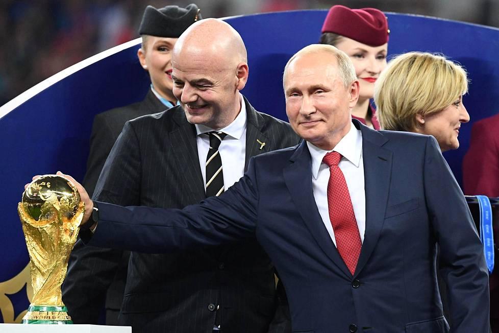 Jalkapallon MM-pokaalia silittämään päässeellä Venäjän presidentti Vladimir Putinilla (oik) on ollut syytä hymyyn onnistuneiden kisajärjestelyjen myötä. Jatko ei näytä kuitenkaan niin positiiviselta, sillä esimerkiksi valtionjohtoiseksi todetun dopingohjelman aiheuttamat sotkut jarruttavat tulevaisuuden kisaisännyyksien myöntämisiä.