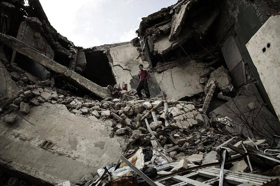 Lapset keräsivät metallia romahtaneesta rakennuksesta Isisin entisessä pääkaupungissa Raqqassa.