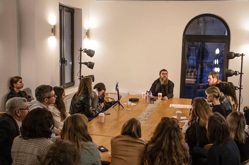 Pöydän päässä istuva Pyhän pappismarttyyri Antipas Pergamonlaisen kirkon kirkkoherra Andrei Štšennikov järjestää kirkon kahvilassa kahden viikon välein tilaisuuden, jossa hän vastaa nuorten kysymyksiin.