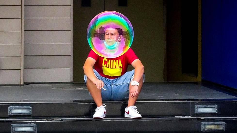 Pekingiläiset käyvät nyt paljon ravintoloissa ja huvituksissa. Kuvan mies on tupakalla elokuvateatterin takana.