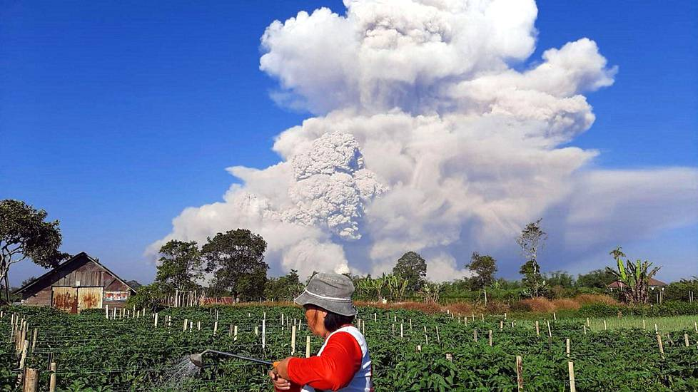 Maanviljelijä hoiti tilaansa tulivuoren purkautuessa.