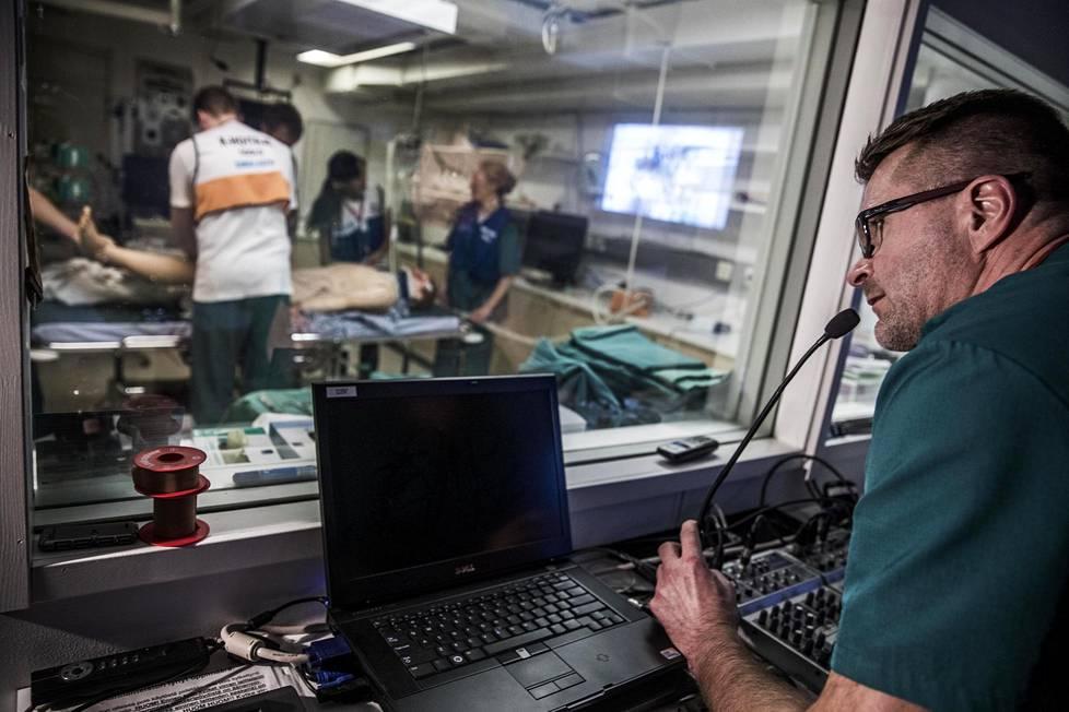 Kirurgi Lauri Handolin ohjaa harjoitusta. Koulutettavat eivät näe häntä lasin takaa, mutta hän näkee kaiken, mitä toisella puolella tapahtuu.