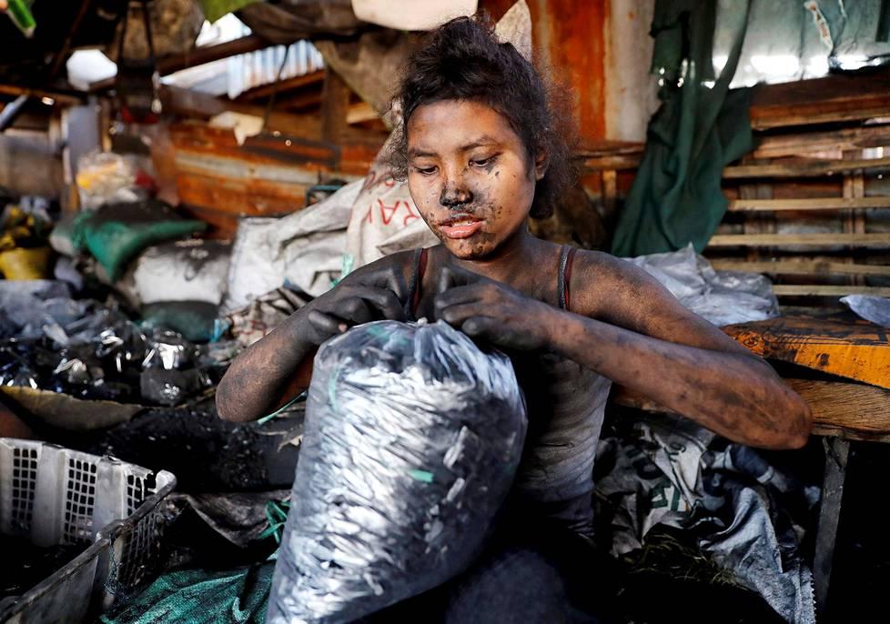 Työntekijä pakkasi hiiliä katuruoan valmistamista varten Manillassa Flippiineillä uudenvuoden aattona.