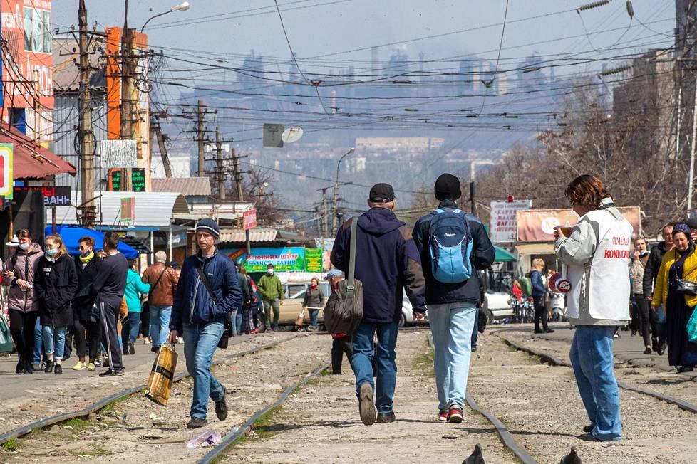 Mariupolin suuret markkinat sijaitsevat huonokuntoisen kadun varrella. Taustalla häämöttää Iljitšin terästehdas, toinen kahdesta suuresta teollisuuslaitoksesta. Markkinoilla osa kauppiaista on kreikkalaista sukujuurta.