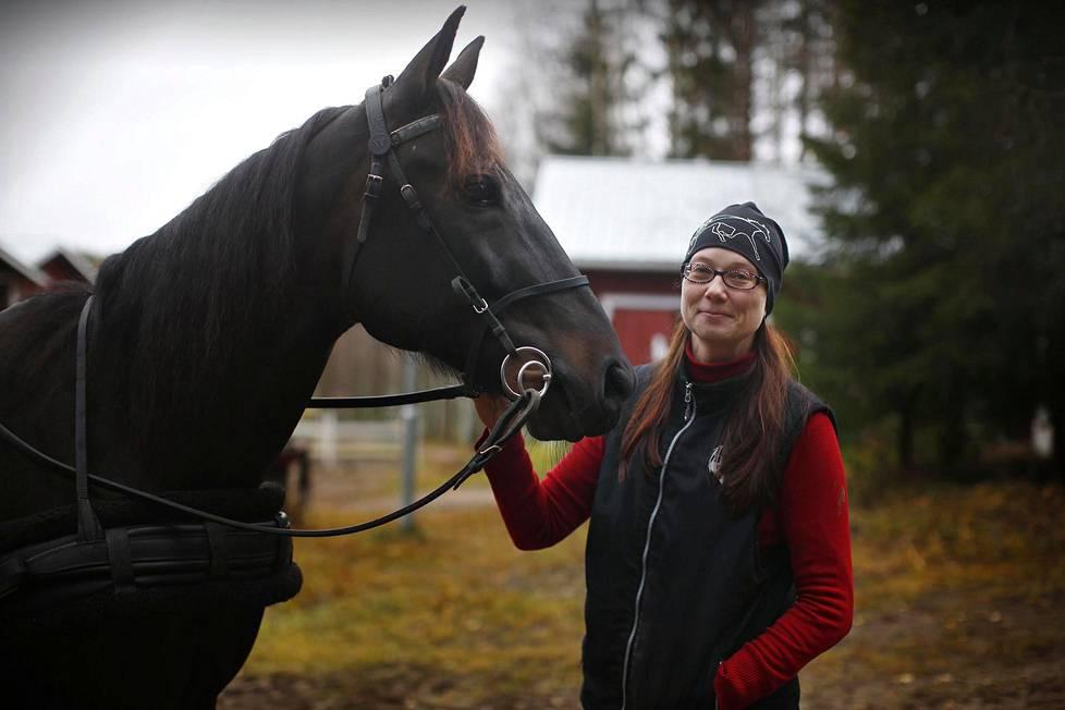 Anne Takapuro pitää kahdentoista hevosen ravitallia Tikkakoskella Keski-Suomessa.