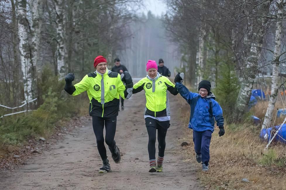 Iina Puskalan mies Mika Puskala ja poika Roni Honkanen saattelivat juoksijan viimeisen maratonin maaliin.