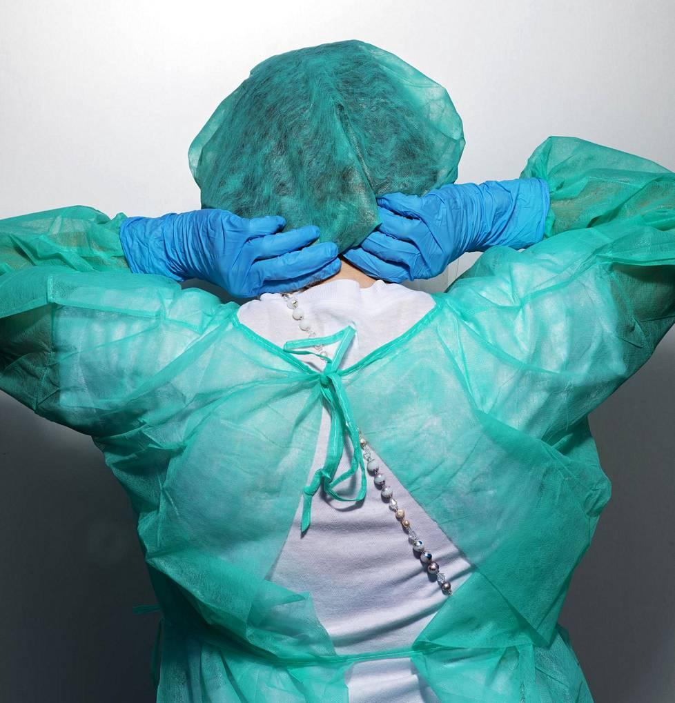 Keuhkoklinikan sairaanhoitaja Pirjo Vitikainen pukeutui suojavarusteisiin.