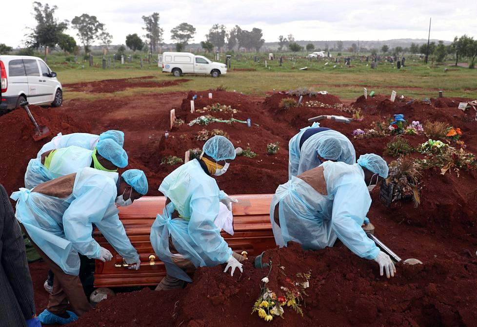 Suojavarusteisiin pukeutuneet hautaustoimiston työntekijät kantoivat koronavirukseen kuolleen arkkua Johannesburgissa Etelä-Afrikassa 6. tammikuuta.