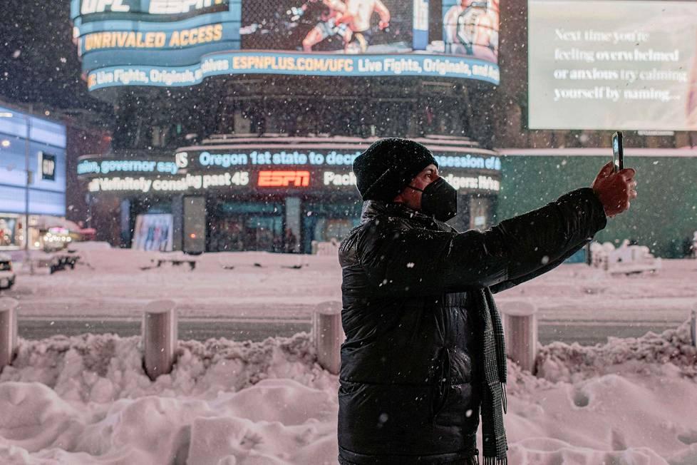 Mies ottaa selfien Times Squarella.