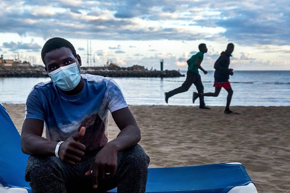 Malilainen Mohammed istui aurinkotuolissa Puerto Ricon hiekkarannalla Gran Canarialla. Hänet on majoitettu turistit menettäneeseen hotelliin.
