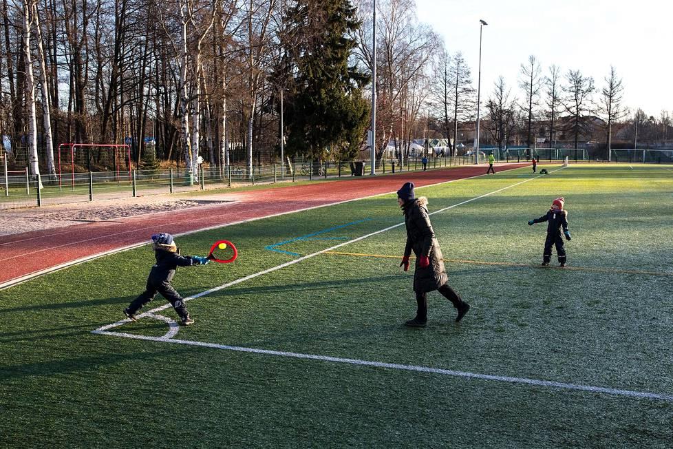Äiti ja kaksoslapset pelaamassa mailapelejä Lauttasaaren urheilukentällä 5. tammikuuta 2020.