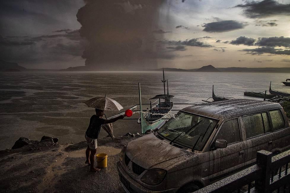 Taalin tulivuori Filippiineillä alkoi purkautua viime vuoden tammikuussa. Tuhkan peittämää autoa huuhdottiin merivedellä. Luontoaiheiset sarjat, 2. palkinto.