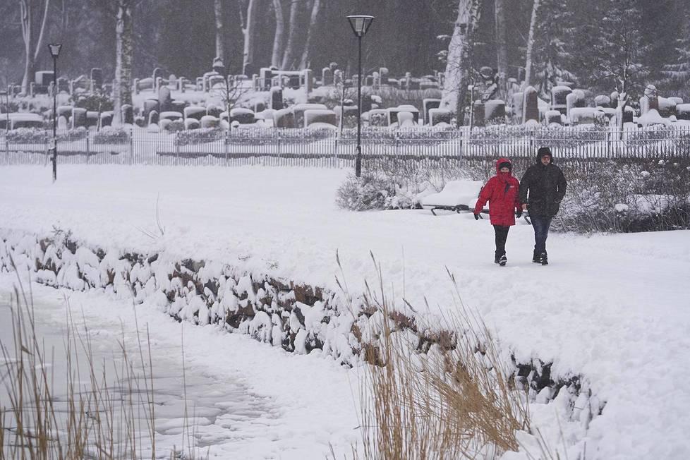 Ulkoilijoita Hietaniemen hautausmaan rannassa 12. tammikuuta 2021.