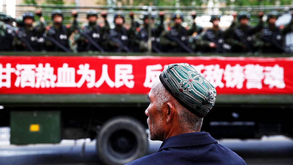 FILE PHOTO: A Uighur man looks on as a truck carrying paramilitary policemen travel along a street during an anti-terrorism oath-taking rally in Urumqi, Xinjiang Uighur Autonomous Region, China May 23, 2014. The Chinese characters on the banner read, Willingness to spill blood for the people. Countering terrorism and fighting the enemies is part of the police spirit.