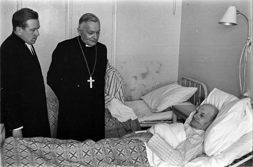 Piispa O. K. Heliövaara (kesk.) tervehti Nätti-Jussia kunnalliskodissa Rovaniemen maalaiskunnassa. Nätti kuoli elokuussa 1964.