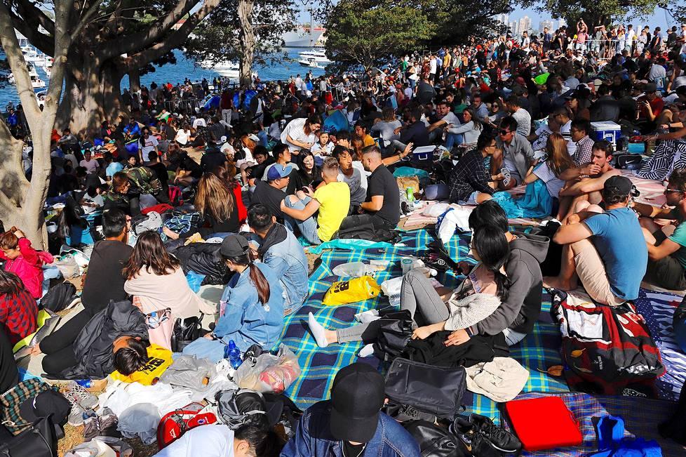 Ihmiset valmistautuivat seuraamaan ilotulitusta Sydneyn satamassa.