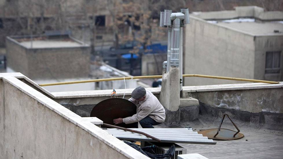 An Iranian man adjusts a satellite dish on a rooftop in northern Tehran January 15, 2011. REUTERS/Morteza Nikoubazl (IRAN - Tags: BUSINESS) - RTXWL68