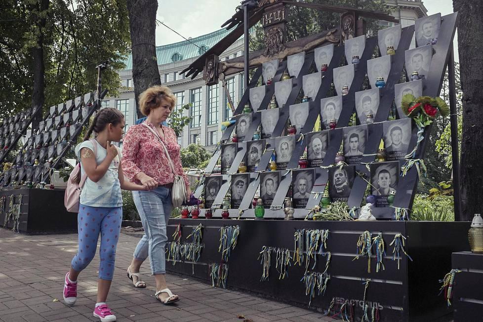 Äiti ja tytär ohittivat Maidanin vuoden 2014 suurmielenosoitusten uhrien muistomerkin keskiviikkona Ukrainan pääkaupungissa Kiovassa.
