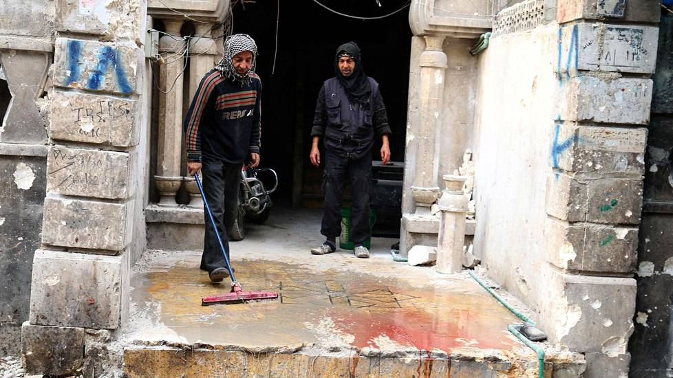 Men wash the blood stained ground after strikes on rebel-held besieged al-Zebdieh district, in Aleppo Syria December 5, 2016. REUTERS/Abdalrhman Ismail - RTSUS4Z