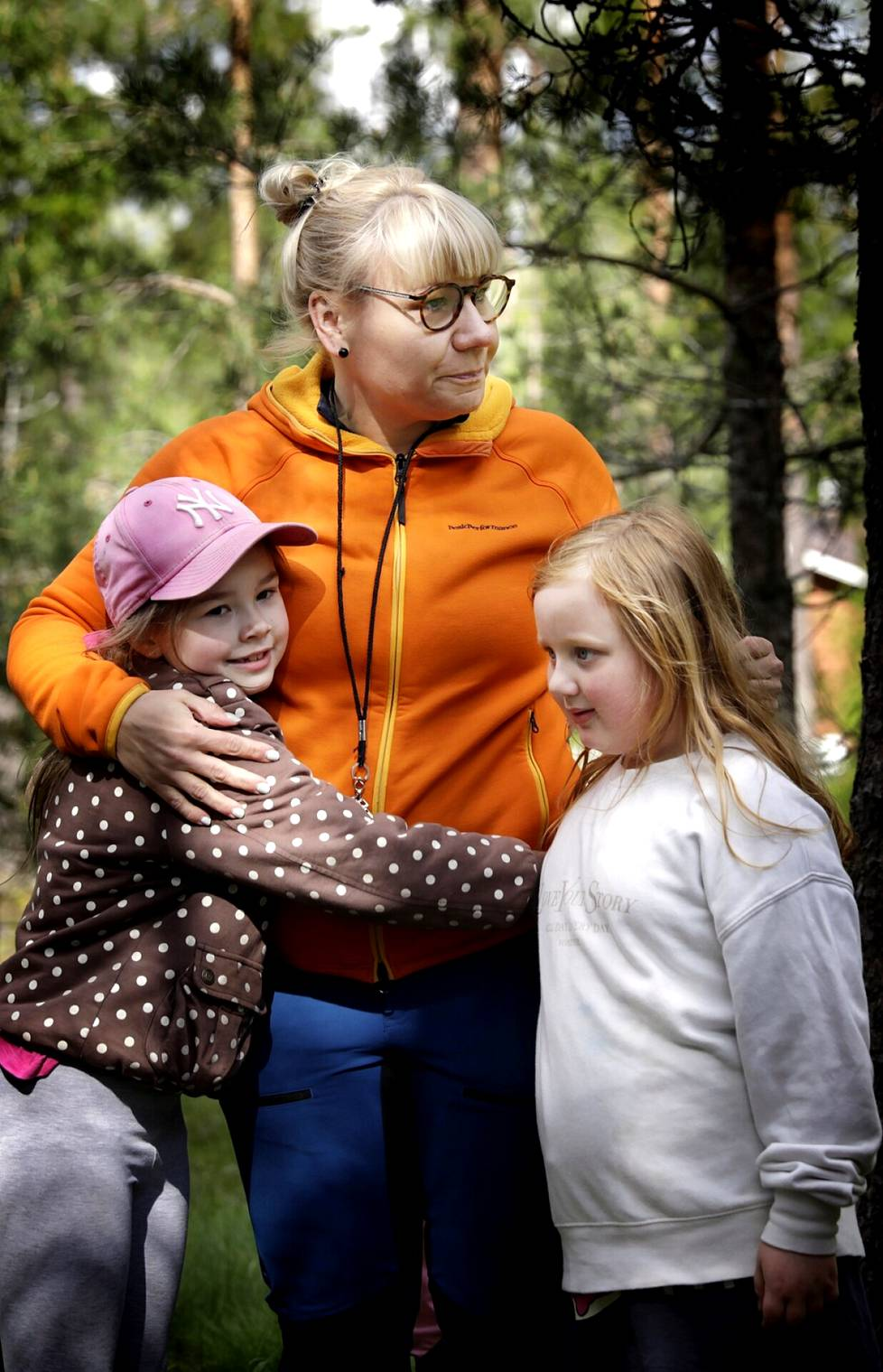 """Johanna Timoselle on tärkeää, että jokainen oppilas kokee olevansa tärkeä. Hän puhuttelee oppilaitaan tämän tästä sanoilla """"rakas"""" tai """"muru"""". Timosen kainalossa Enni Suo (vas.) ja Lilli Hannila."""