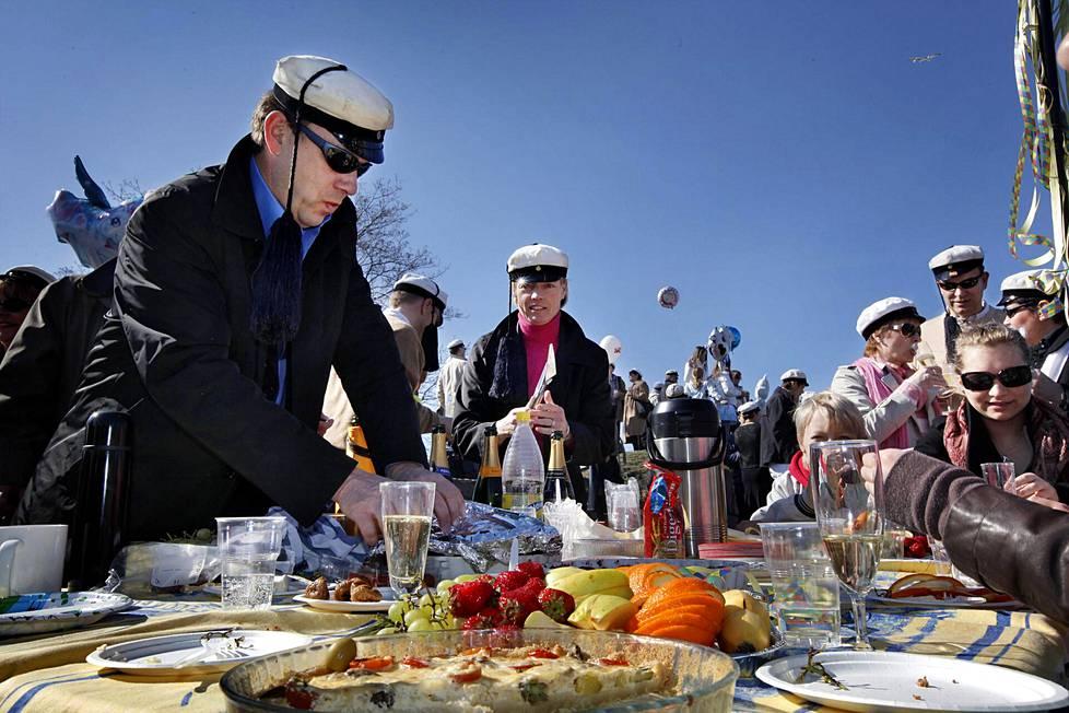 Jukka Auramo kattaa Gluttons Gourmet -seurueen piknikpöytään tomaattipiirakkaa Ullanlinnanmäellä vuonna 2009.
