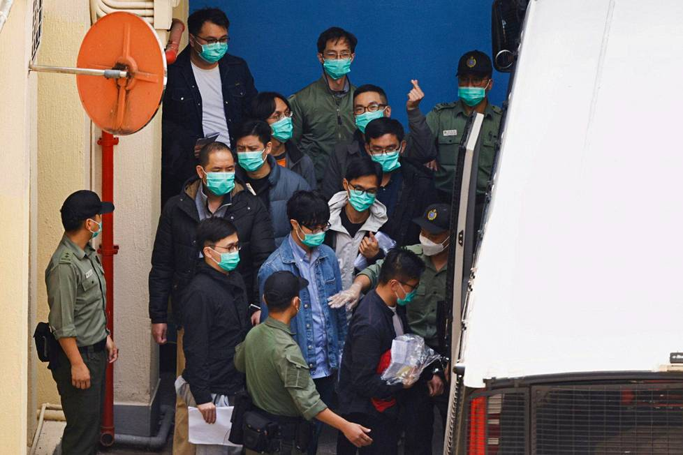 Viranomaiset saattelivat demokratia-aktivisteja tiistaina putkabussiin, joka vei heidät oikeuteen vastaamaan Hongkongin turvallisuuslain rikkomista koskeviin syytteisiin.