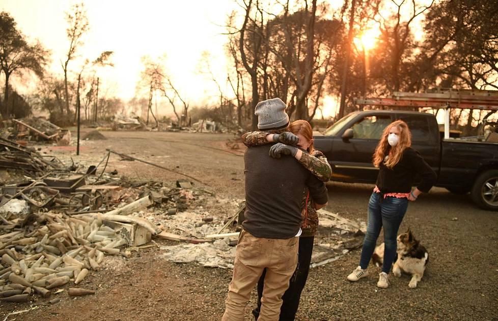 Kimperly Spainhower halasi miestään Ryan Spainhoweria sunnuntaina Paradisessa Kaliforniassa. Tytär Chloe Spainhower katsoi perheen kodin palaneita raunioita.