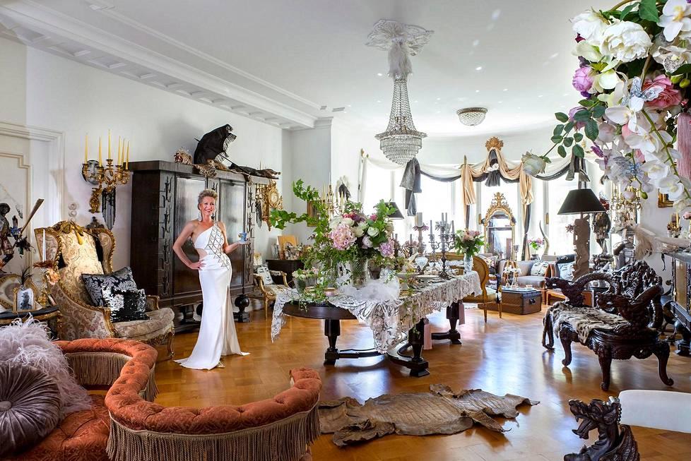 Etualalla Fästmans-sohva, jollaisissa naimattomat pariskunnat saattoivat aikoinaan istua. Lattialla on krokotiilin vuota. Kiinalaista 1900-luvun alun ruusupuutuolia koristavat lohikäärmeet. Kukka-asetelmat on suunnitellut Tanja Lähdeaho Flora & Moresta. Charlotta Vilamon valkoinen iltapuku on Versacen muotitalosta.