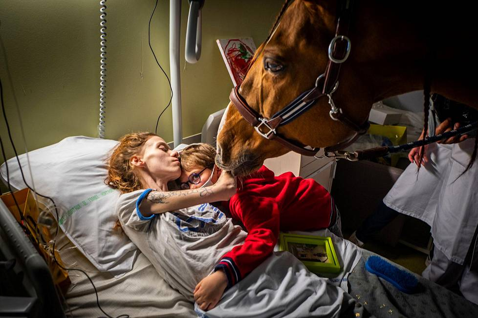 Parantumatonta syöpää sairastavan Manonin hoidossa Ranskan Calaisissa käytetään eläinterapiaa. Manonin kainalossa on hänen 7-vuotias poikansa Ethan, ja etualalla Peyo-hevonen. Ajankohtaiset aiheet, 2. palkinto.