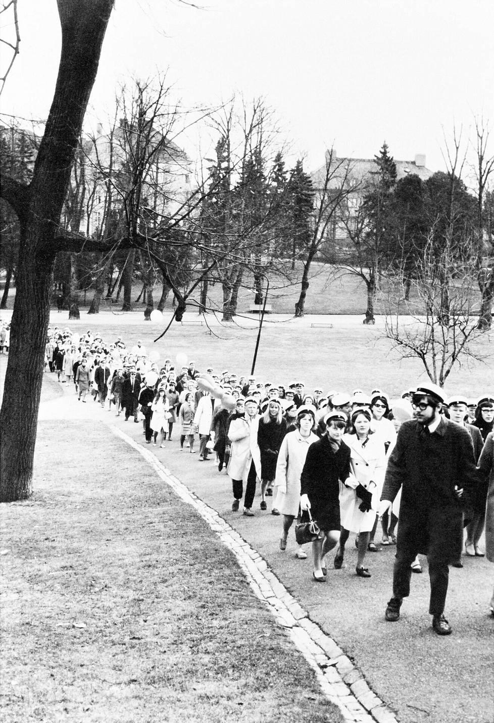Ylioppilaat kiipeävät Ullanlinnanmäelle Kaivopuistossa vappupäivän aamuna vuonna 1968.