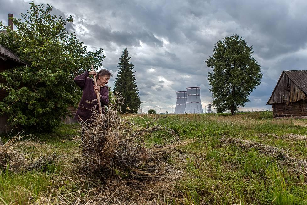 Astravetsin ydinvoimalan naapurikylässä asuva Maria Šartvetene haravoi takapihallaan.