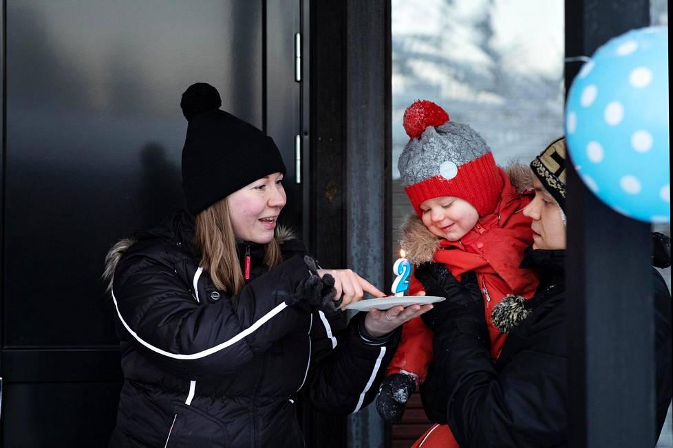 Benjamin Jantunen puhaltaa pannukakkupalaan pystytetyn kynttilän vanhempiensa Mia ja Heikki Jantusen avulla.