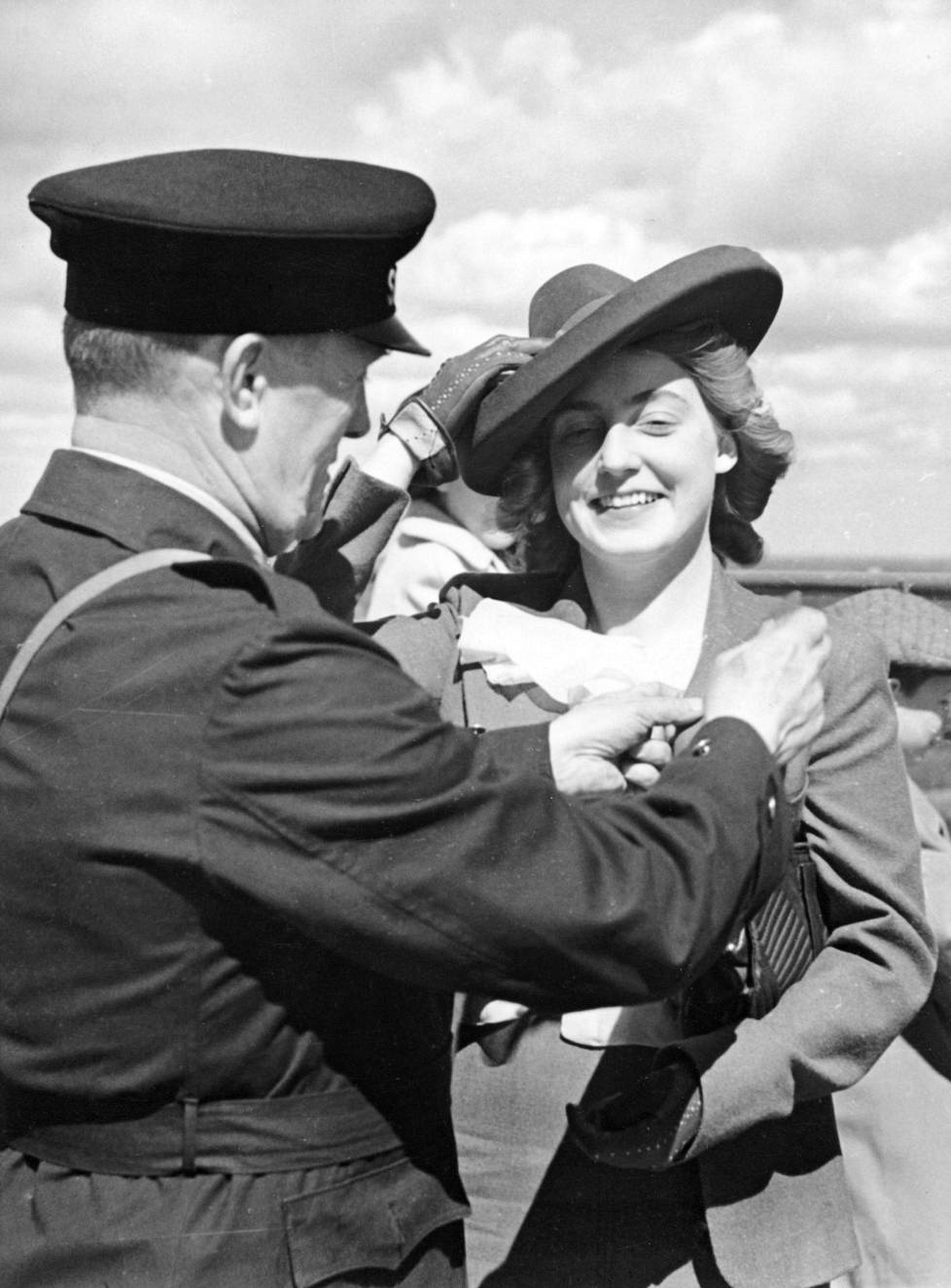 Albin Stenroos attaches a golden tower badge to the costume of Liisa Heilimo from Vyborg.  Heilimo was 100,000 visitors to the Olympic Stadium tower on May 21, 1939.