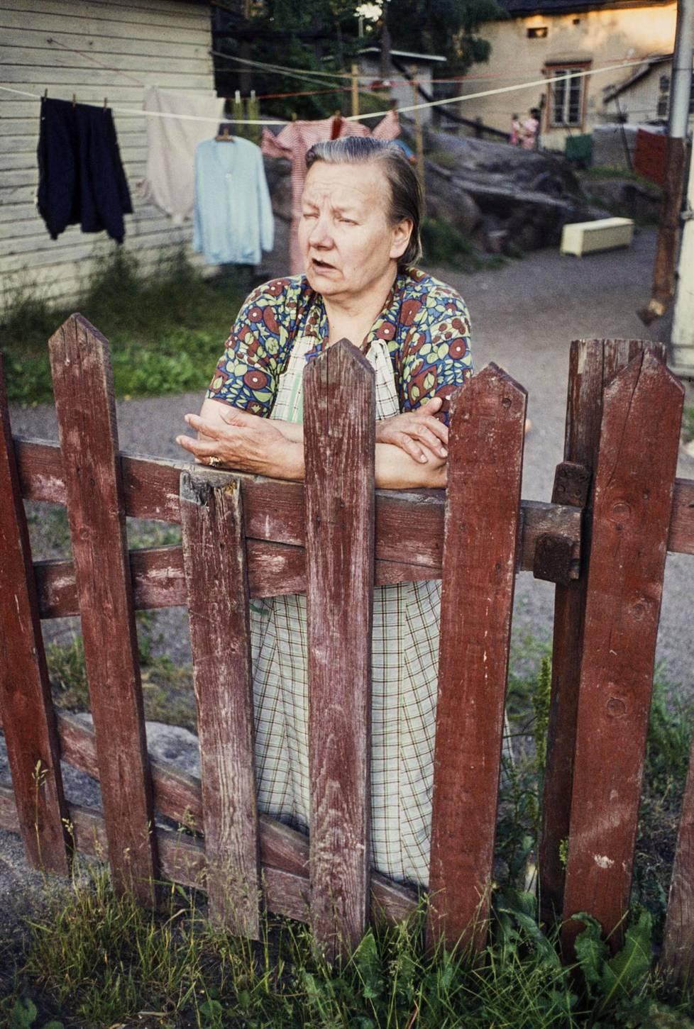 Nainen nojasi porttiin Puu-Pasilassa. Kuva on otettu 1970-luvulla.