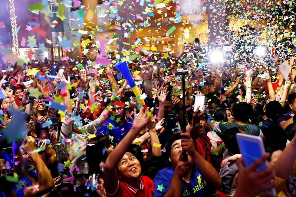 Ihmiset juhlivat uutta vuotta kauppakeskuksessa Manillassa.