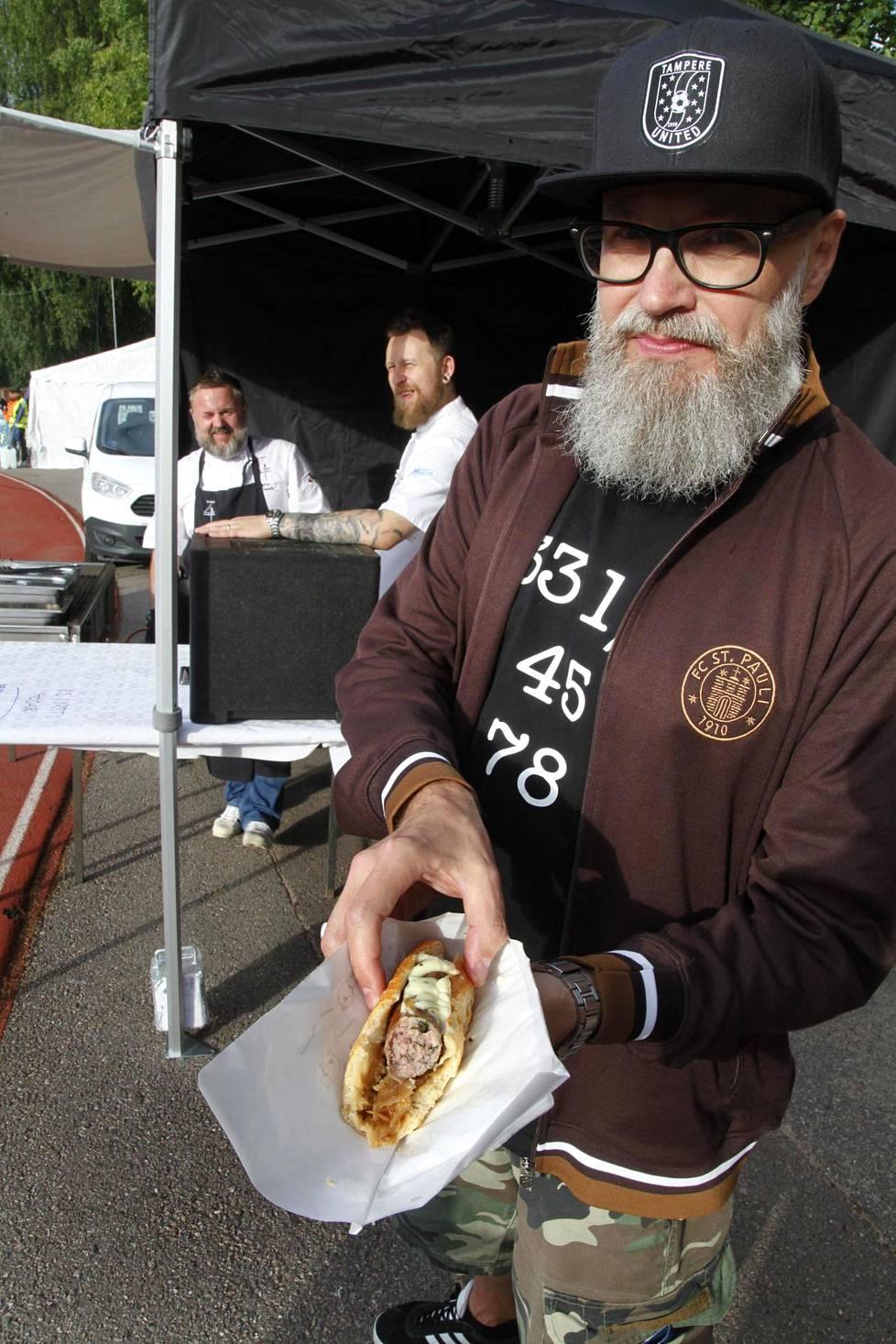 Rami Siikanivalle maistui yrttimakkaralla täytetty hodari. Taustalla kokit Yoni Ichtertz ja Juho Rajamäki.