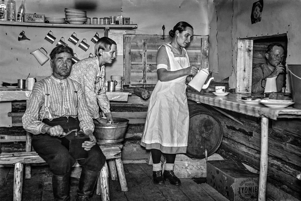 Savotan emäntä eli kokki Tyyne Välitalo (oik.) kaataa kahvia savottakämpän keittiössä. Ruokaa ja juomaa tarjoiltiin niin sanotusta elämänluukusta. Välitalon apulainen tiskaa. Hänen nimensä ei ole tiedossa. Kämppämies Taavetti Mykkänen jauhaa myllyllä kahvinpapuja. Pöydän alla on Työmies-tupakkaa sisältävä iso laatikko ja kotikaljatynnyri. Kotikalja oli hyvän säilyvyytensä ansiosta tavallinen ruokajuoma savotoilla. Kämpän nimi ja kuvanottoaika ei ole tiedossa.