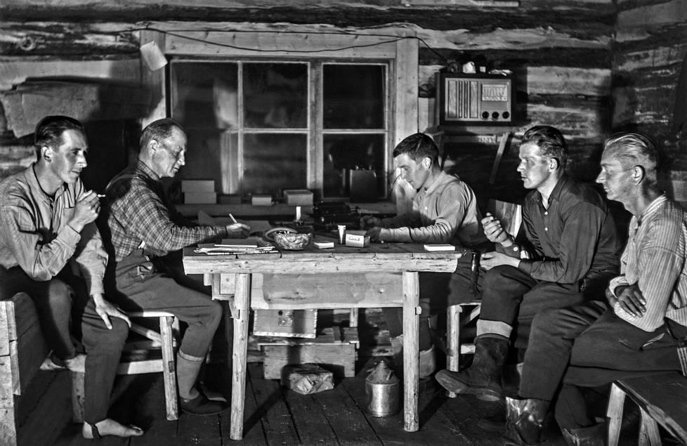 Valokuvausta harrastanut Matti Körkkö (kesk.) toimi savotoilla kasöörinä eli kassanhoitajana. Pöydällä hänen edessään on laskukone. Hän majoittui ja työskenteli savottakämpän terävässä päässä eli työjohdon tiloissa. Muut tilat olivat miehistöpää ja keittiö emännänhuoneineen. Savotan johtaja eli ukkoherra Niilo Porthen istuu Körkköä vastapäätä. Vasemmalla istuu Eino Kantolainen, oikealla Pekka Paakkunainen ja Kalle Toratti. Ikkunan viereen seinälle on ripustettu radio, joka sai virtansa akusta.