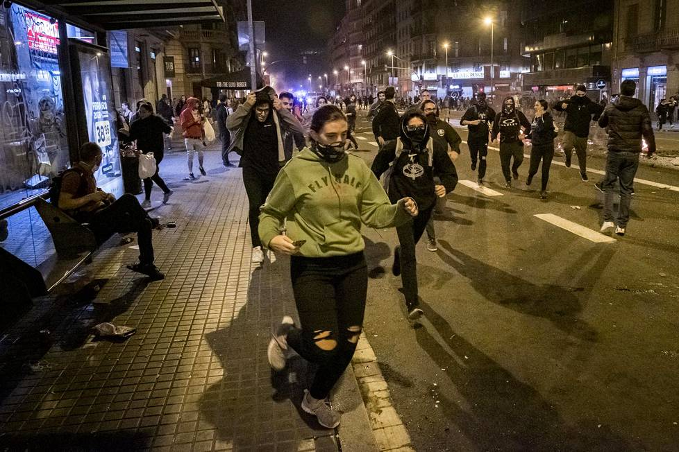 Joukko mielenosoittajia juoksi pakoon mellakkapoliisia Barcelonan keskustassa perjantain ja lauantain välisenä yönä.