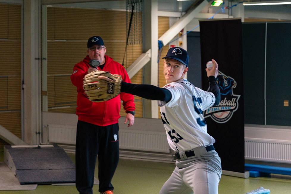 Pesäpalloilija Konsta Kurikka hioi baseballsyöttöään tiistaina Espoon Leppävaarassa. Baseball- ja softball-liiton puheenjohtaja Jukka Ropponen mittasi taustalla heittojen nopeuksia.